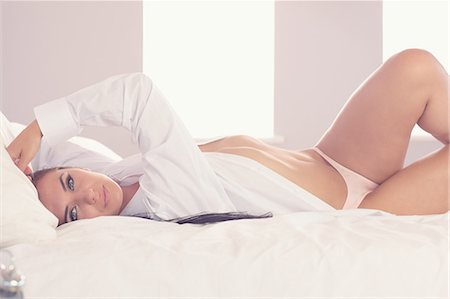 pretty - Attractive woman stretching out on her bed looking at camera wearing a white shirt Stock Photo - Premium Royalty-Free, Code: 6109-07497737