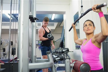Calm brunette training at weight machine in weights room of gym Stock Photo - Premium Royalty-Free, Code: 6109-07497848