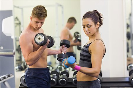 slim - Determined man and woman holding dumbbells in weights room of gym Stock Photo - Premium Royalty-Free, Code: 6109-07497947