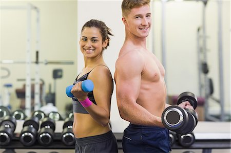 slim - Topless man and smiling woman holding dumbbells in weights room of gym Stock Photo - Premium Royalty-Free, Code: 6109-07497944