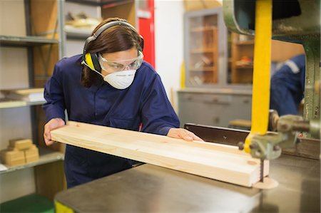 Trainee wearing safety protection using saw in workshop Stock Photo - Premium Royalty-Free, Code: 6109-07497998