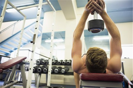 Muscular man holding heavy dumbbell over head in weights room of gym Stock Photo - Premium Royalty-Free, Code: 6109-07497904