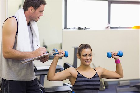Instructor taking notes of happy brunette lifting dumbbells in weights room of gym Stock Photo - Premium Royalty-Free, Code: 6109-07497931