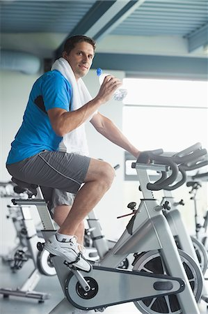 Side view portrait of a tired young man with water bottle working out at spinning class in gym Stock Photo - Premium Royalty-Free, Code: 6109-07498043