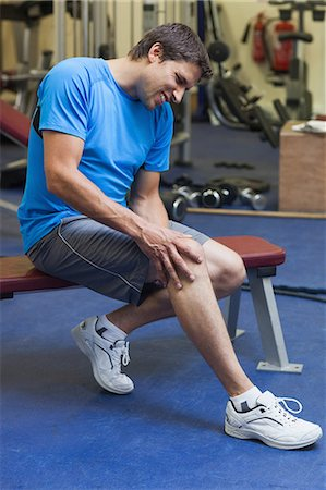 Side view of a healthy young man with an injured leg sitting in the gym Stock Photo - Premium Royalty-Free, Code: 6109-07498064