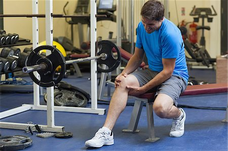 Full length of a healthy young man with an injured leg sitting in the gym Stock Photo - Premium Royalty-Free, Code: 6109-07498065