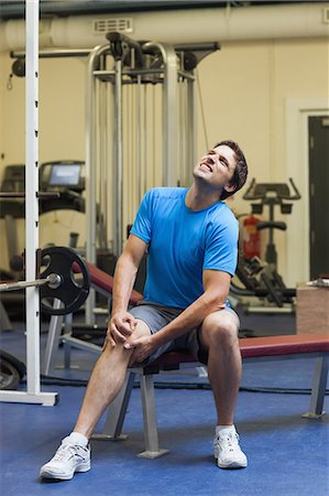 Full length of a healthy young man with an injured knee sitting in the gym Stock Photo - Premium Royalty-Free, Code: 6109-07498066
