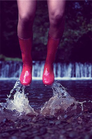 Close up low section of a woman in red gumboots jumping in water Stock Photo - Premium Royalty-Free, Code: 6109-07498076