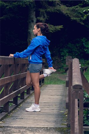 Full length side view of a healthy young woman stretching her leg during exercise on footbridge Stock Photo - Premium Royalty-Free, Code: 6109-07498082