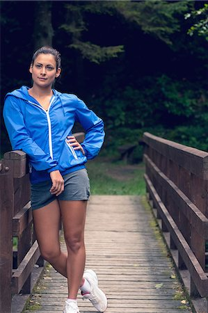 Full length of a healthy young woman standing on footbridge during exercise Stock Photo - Premium Royalty-Free, Code: 6109-07498085
