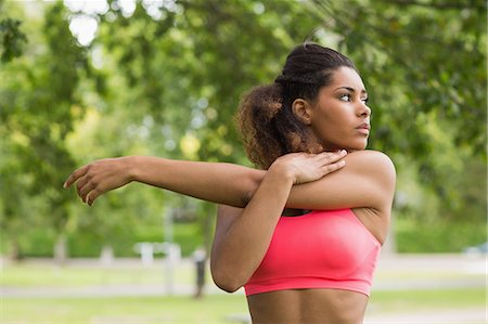 Serious healthy young woman stretching her hand during exercise at the park Stock Photo - Premium Royalty-Free, Code: 6109-07498030