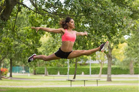 Full length of a toned young woman performing the splits jump in the park Stock Photo - Premium Royalty-Free, Code: 6109-07498038