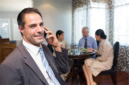 Businessman using cellphone with colleagues having meal Stock Photo - Premium Royalty-Free, Code: 6109-07600847