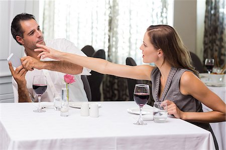 Couple with wine glass and cellphone arguing in restaurant Stock Photo - Premium Royalty-Free, Code: 6109-07600967