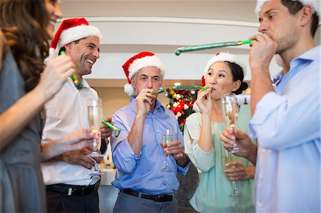 People in Santas hats with champagne flutes and noise makers Stock Photo - Premium Royalty-Free, Code: 6109-07600931