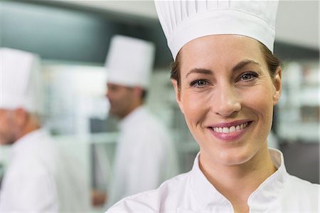 Smiling chef looking at camera with team working behind Stock Photo - Premium Royalty-Free, Code: 6109-07601050