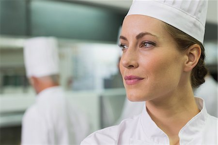 Serious chef looking away with team working behind Stock Photo - Premium Royalty-Free, Code: 6109-07601051