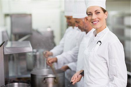 Happy chef smiling at camera while cooking at stove Stock Photo - Premium Royalty-Free, Code: 6109-07601055