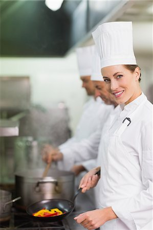 Happy chef smiling at camera while cooking at stove Stock Photo - Premium Royalty-Free, Code: 6109-07601056
