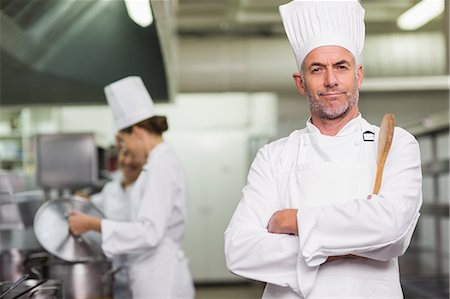 Head chef looking at camera holding wooden spoon Stock Photo - Premium Royalty-Free, Code: 6109-07601063
