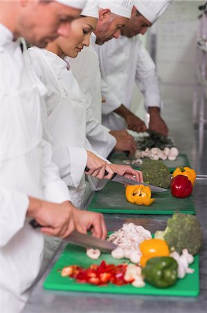 Row of trainee chefs slicing vegetables Stock Photo - Premium Royalty-Free, Code: 6109-07601084
