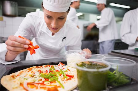 Chef sprinkling pepper on a pizza Stock Photo - Premium Royalty-Free, Code: 6109-07601097