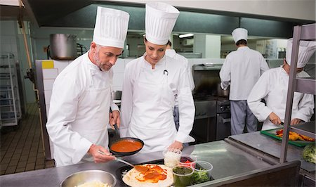Head chef showing trainee how to prepare pizza Stock Photo - Premium Royalty-Free, Code: 6109-07601095