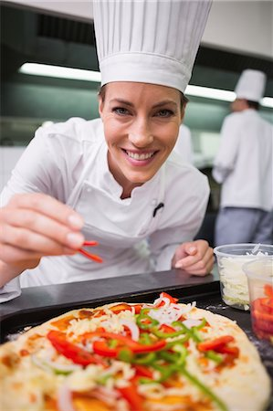 restaurant - Happy chef sprinkling pepper on a pizza Stock Photo - Premium Royalty-Free, Code: 6109-07601098