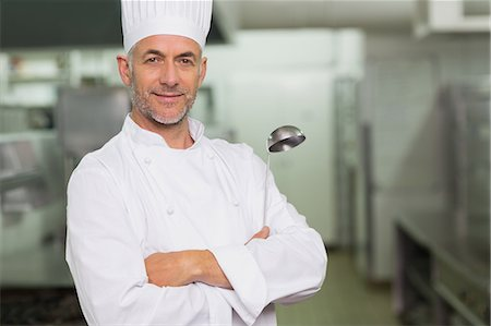 Confident chef with arms crossed holding a ladle Stock Photo - Premium Royalty-Free, Code: 6109-07601037