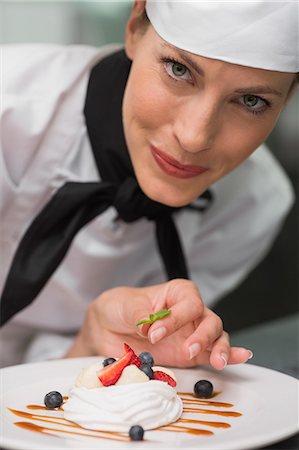Smiling chef putting mint leaf on meringue dish Stock Photo - Premium Royalty-Free, Code: 6109-07601141