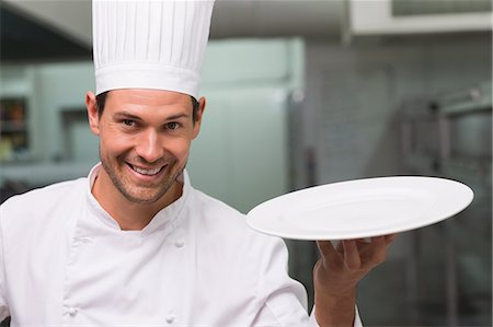 Chef holding a plate smiling at camera Stock Photo - Premium Royalty-Free, Code: 6109-07601170