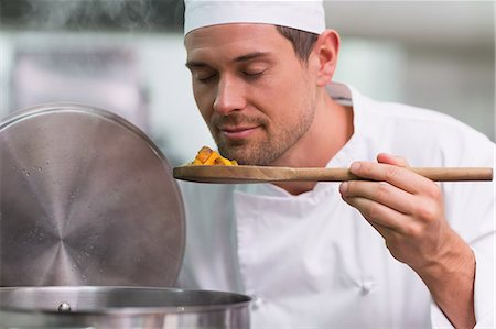 Chef smelling a spoon of food from the pot Stock Photo - Premium Royalty-Free, Code: 6109-07601172