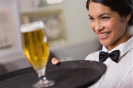 Pretty waitress holding tray with glass of beer Stock Photo - Premium Royalty-Free, Code: 6109-07601192