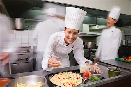 Happy chef preparing a pizza Stock Photo - Premium Royalty-Free, Code: 6109-07601100