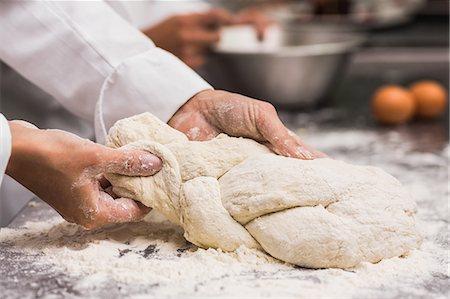 Chef plaiting dough at counter Stock Photo - Premium Royalty-Free, Code: 6109-07601115