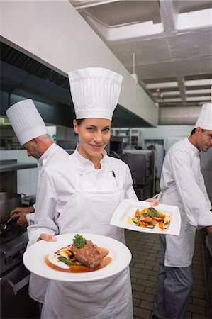 Happy chef holding steak dinner and salmon dinner Stock Photo - Premium Royalty-Free, Code: 6109-07601131