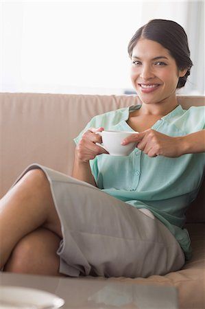 sitting - Happy businesswoman having coffee sitting on sofa Stock Photo - Premium Royalty-Free, Code: 6109-07601208