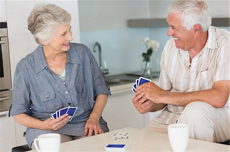 Happy senior couple playing a card game Stock Photo - Premium Royalty-Free, Code: 6109-07601391