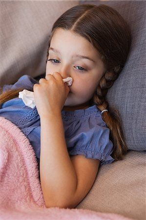 Close-up of a girl blowing nose with tissue paper Stock Photo - Premium Royalty-Free, Code: 6109-07601488