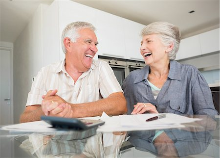 domestic life - Happy couple using the calculator to pay bills Stock Photo - Premium Royalty-Free, Code: 6109-07601407