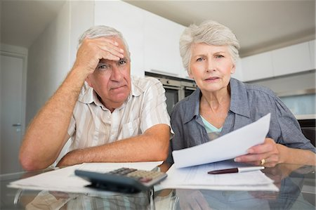 domestic life - Worried couple paying their bills looking at camera Stock Photo - Premium Royalty-Free, Code: 6109-07601408
