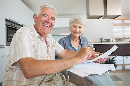 domestic life - Happy couple paying their bills at the table Stock Photo - Premium Royalty-Free, Code: 6109-07601409