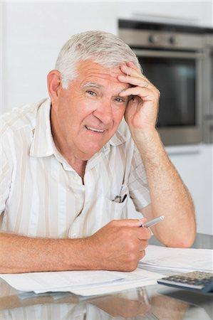 Worried senior man paying his bills Stock Photo - Premium Royalty-Free, Code: 6109-07601417