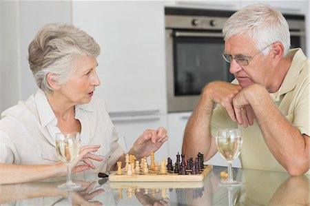 setting kitchen table - Smiling senior couple playing chess and having white wine Stock Photo - Premium Royalty-Free, Code: 6109-07601423