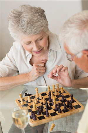 setting kitchen table - Smiling senior couple playing chess and having white wine Stock Photo - Premium Royalty-Free, Code: 6109-07601425