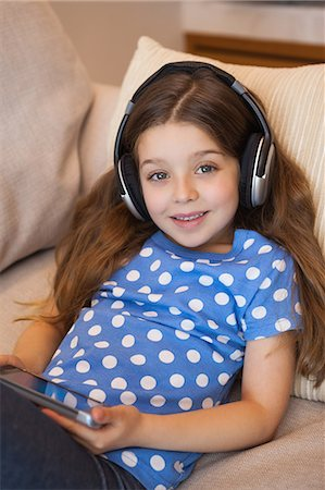 pretty - Little girl listening music while using digital tablet in living room Stock Photo - Premium Royalty-Free, Code: 6109-07601513