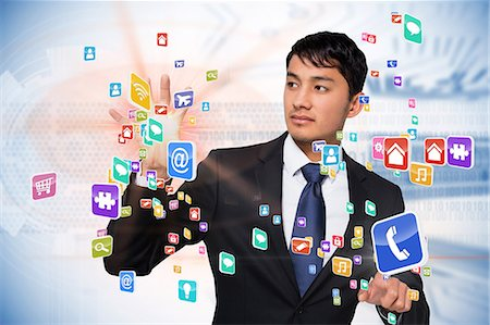 Asian businessman touching app interface Stock Photo - Premium Royalty-Free, Code: 6109-07601600