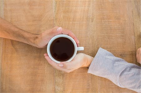 Two hands holding a cup of coffee on wooden table Stock Photo - Premium Royalty-Free, Code: 6109-08203254