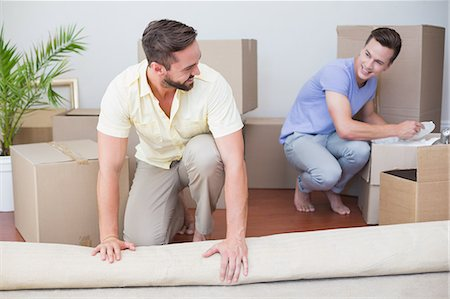 Handsome man unrolling carpet with his boyfriend behind Stock Photo - Premium Royalty-Free, Code: 6109-08203687