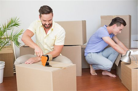 Handsome man packing box with his boyfriend behind Stock Photo - Premium Royalty-Free, Code: 6109-08203685